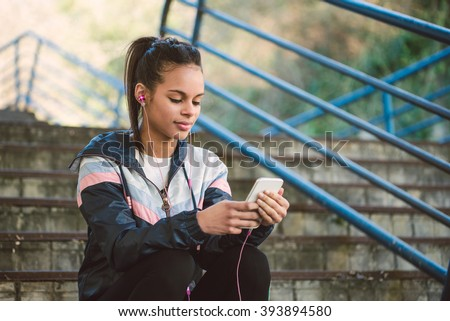 Beautiful hispanic woman listen music after running on a stairs - stock photo