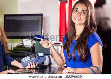 Beautiful Hispanic woman paying with a credit card at a clothing store - stock photo