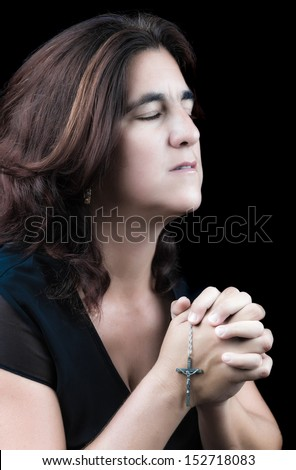 Beautiful hispanic woman praying with her eyes closed and holding a small crucifix (side view, isolated on black)