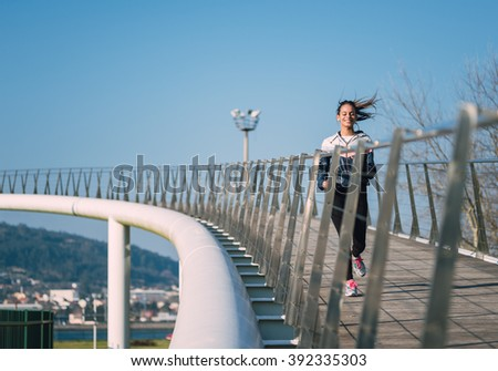 Beautiful hispanic woman running on a bridge outdoors