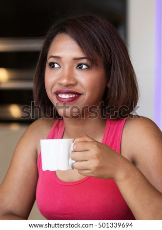 beautiful hispanic woman sitting at table and drinking coffee
