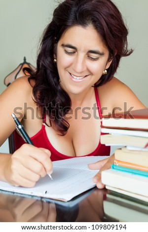 Beautiful hispanic woman writing in a notebook with a pile of books on her desk - stock photo