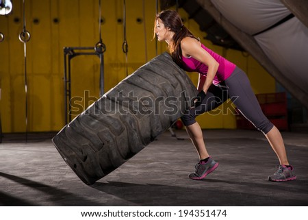 Beautiful Hispanic young woman halfway from flipping a tire in a cross-training gym - stock photo