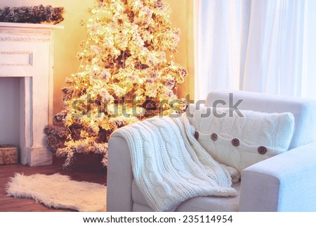 Beautiful holiday decorated room with Christmas tree and white comfortable chair with soft knitted blanket and cushion on it - stock photo