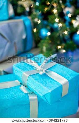 Beautiful holiday decorated room with Christmas tree with presents under it. Color blue
