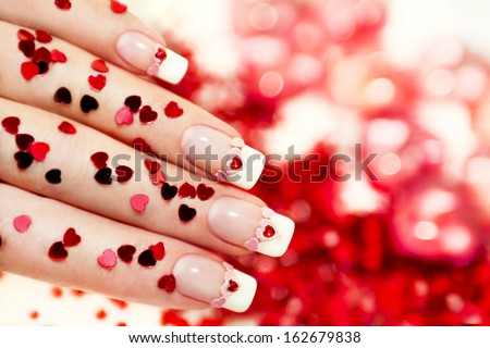 Beautiful holiday manicure with a red heart and with sparkles in the shape of a heart in my hand, and background. - stock photo