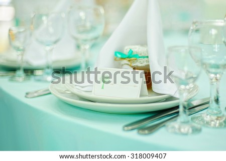 Beautiful holiday table setting in white and blue color with a gift on the plate