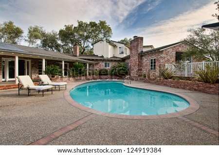Beautiful home and patio, pool and lounge chairs - stock photo