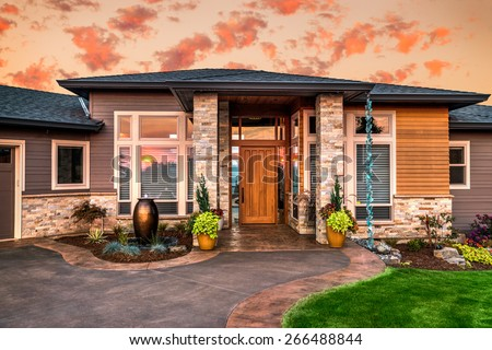 Beautiful Home Exterior at Sunset: Luxury House with Columns, Lawn, Sliver of a Garage, and Sunset Reflection in Windows - stock photo