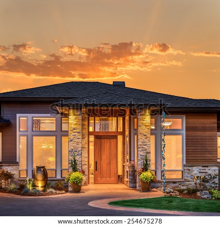 Beautiful Home Exterior at Sunset/Sunrise with Glowing Orange Sky  - stock photo