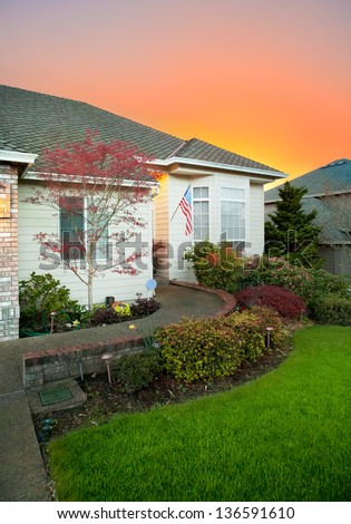 Beautiful Home Exterior with Gorgeous Sunset Backdrop and US Flag - stock photo
