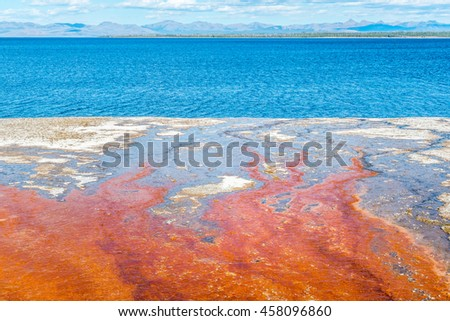 Beautiful hot spring surrounded by colorful layers of red bacteria, against cloudy blue sky - stock photo