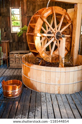 Beautiful hot tub in the garden with a watermill inside of it. - stock photo