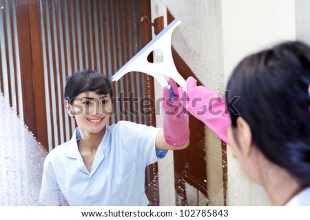 Beautiful Hotel maid wearing pink gloves cleaning up the bathroom