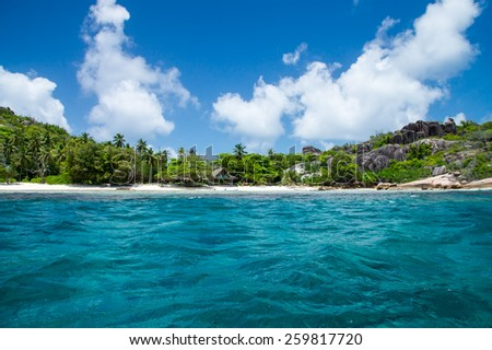 Beautiful hotel on the shore of the turquoise waters of the ocean. Surrounded by tropical greenery. The Seychelles. - stock photo