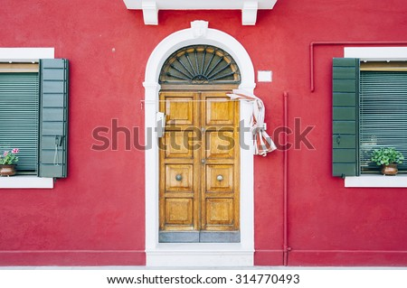 Beautiful house facade on Burano island in the north Italy. Red damaged wall with a wooden old door and two green windows