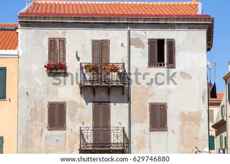 Beautiful house facade with windows and wooden shutters in Alghero, Italy