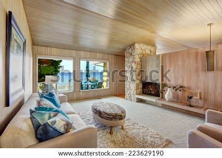Beautiful house interior with wooden plank trim and fireplace. Comfortable couch, soft fur rug and ottoman create romantic atmosphere - stock photo