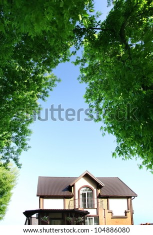 Beautiful house under the arch of trees in the background of the summer sky. - stock photo