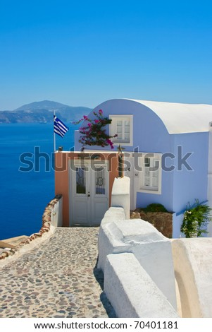 Beautiful house with greece national flag on the street in Santorini, Oia. Aegean sea in a background, Greece.