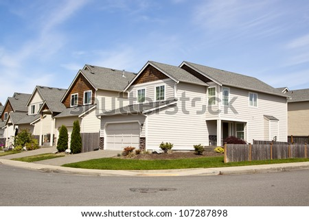 beautiful houses with blue sky and lush landscape - stock photo