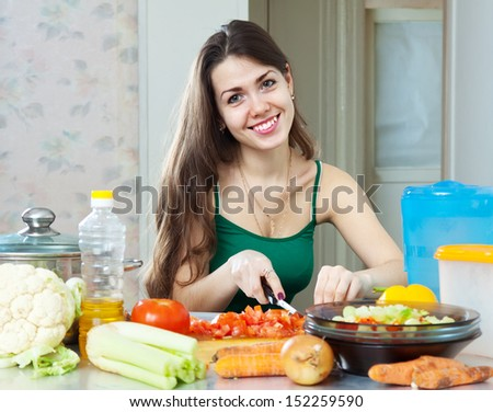 beautiful housewife cuts tomato at her kitchen at home - stock photo