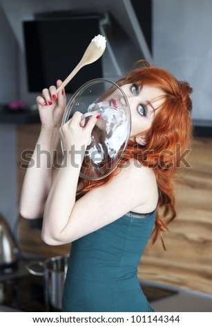 Beautiful housewife licking a pot cover - stock photo