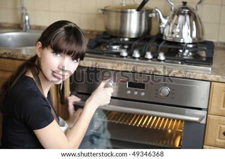 Beautiful housewife switching the oven