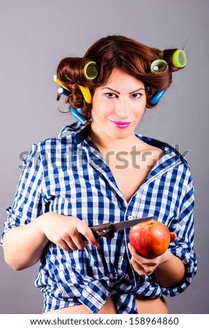 beautiful housewife with curlers holding apple and the knife - stock photo