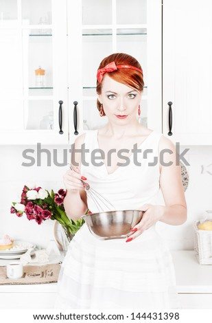 Beautiful housewife with utensils - stock photo