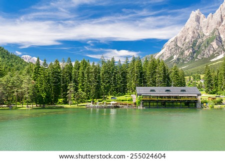 Beautiful hut over the lake in the middle of mountains valley. - stock photo