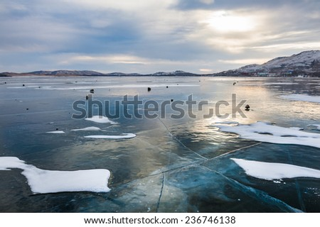 Beautiful ice on the lake at sunset. Winter landscape