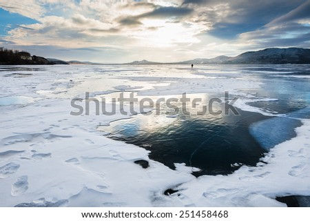 Beautiful ice on the lake at sunset. Winter landscape - stock photo