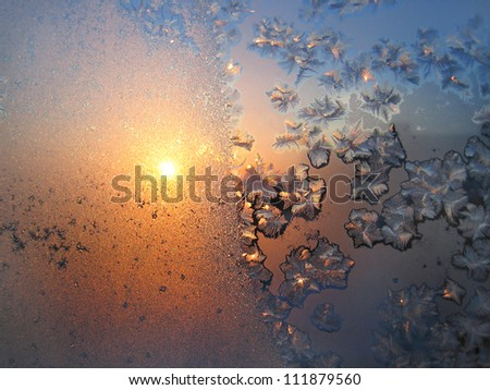 Beautiful ice pattern and sunlight on winter glass - stock photo