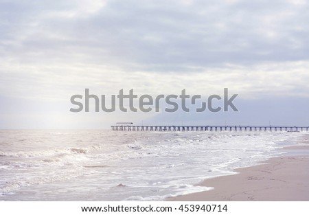 Beautiful idyllic beach landscape in soft muted colors, with added sun flare and retro vintage style filters.  - stock photo