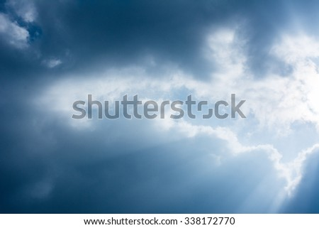 Beautiful image Fantastic sun rays striking through clouds in blue sky for Background - stock photo
