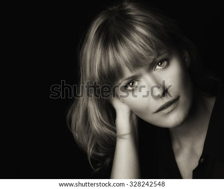 Beautiful Image of a Blond woman On Black in studio - stock photo
