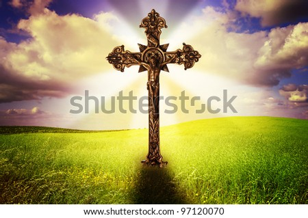 Beautiful image of a cross in a grass field with a holy cloudy sky - stock photo