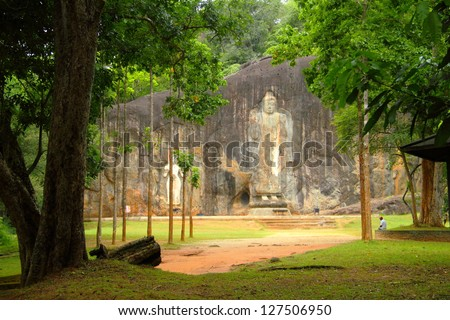 Beautiful image of carved Buddhist Sculpture Rock in Buduruvagala (UNESCO World Heritage Site), view from wood - one of the most mysterious and interesting tourist sightseeing in Sri Lanka, South Asia - stock photo