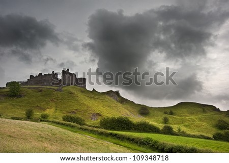Beautiful image of medieval castle ruins in landscape with moody sky background - stock photo