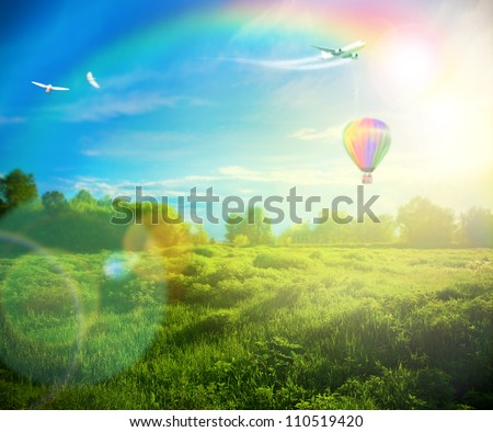 Beautiful image of stunning sunset with atmospheric clouds and sky over vibrant fields in  countryside landscape with hot air balloon, birds and airplane flying high - stock photo