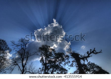 Beautiful image of Sun light beams coming from behind cloud, blue sky and trees , a natural phenomenon. Stock image shot at Sikkim, West Bengal, India - stock photo