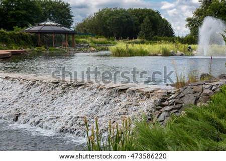 Beautiful image on cascade of water flowing from pond in park