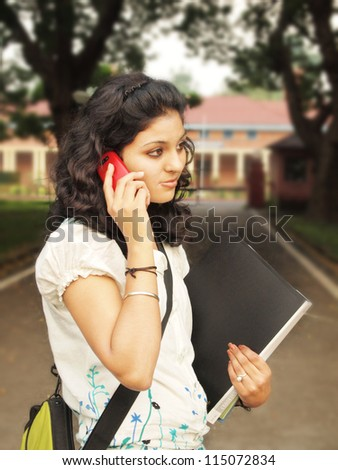 Beautiful Indian / Asian colege student talking on her Cellphone. - stock photo