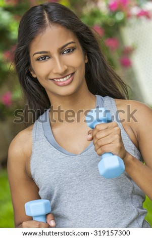 Beautiful Indian Asian young woman or girl running exercising with weights outside in summer sunshine with perfect teeth and long hair - stock photo