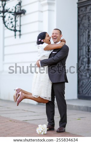 Beautiful indian bride and caucasian groom,  after wedding ceremony. Happy couple in love, celebrating wedding. - stock photo