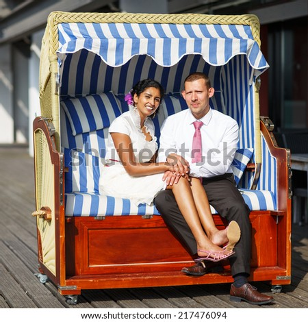 Beautiful indian bride and caucasian groom, in beach chair. Woman and man in love.  Square size. - stock photo
