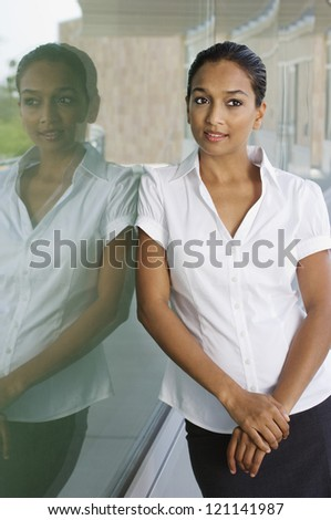 Beautiful Indian business woman contemplating while leaning on glass