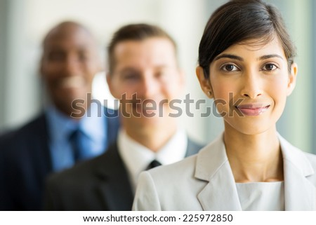 beautiful indian businesswoman standing in a row with colleagues - stock photo