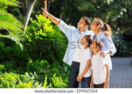 beautiful indian family looking and pointing in the park - stock photo